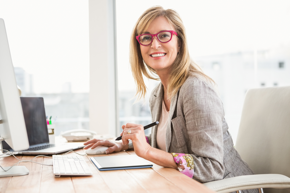 Portrait of smiling casual designer using computer and digitizer in the office